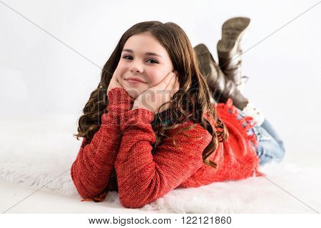 Cute stylish caucasian tween girl laying on ground smiling