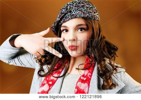 Cute stylish caucasian tween makes peace gesture