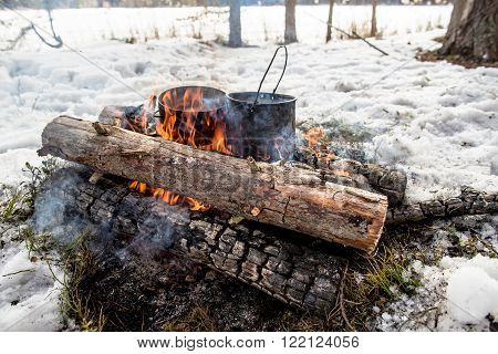 Cooking in a winter hike in the cauldron hanging over the fire in the snow-covered pine forest while camping from the boiler coming vapor