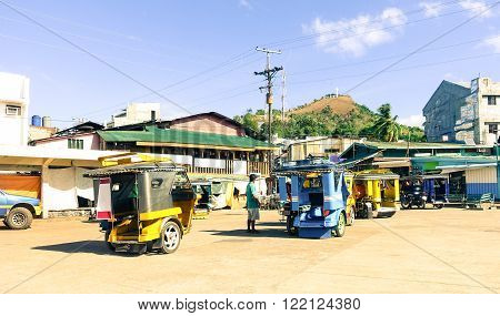 CORON,PHILIPPINE - FEBRUARY , 9 2016: tricycles taxi in Coron Town central square waiting for tourists - Popular Philippines crafted taxi vehicle with mountain Tapyas in background  on February 9 , 2016  in Coron , Palawan , Philippines