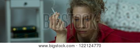 Panorama of unhappy lonely woman lying with cigarette