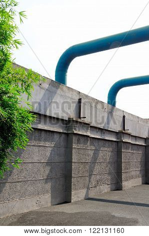 A stone wall and large blue ventilation duct piping outside in M50 area of Shanghai China.