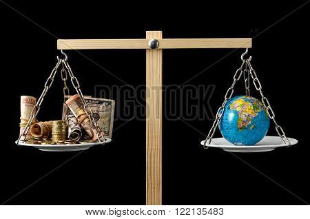 Globe Planet Earth and Money on a Two Pan Balance