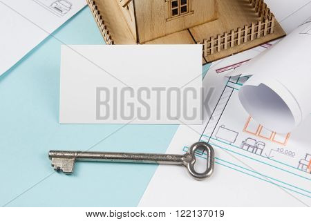 Real estate. Silver key with house figure and blank business card on blue print background. Top view