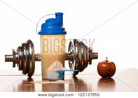 Whey protein powder in scoop dumbbell meter tape and plastic shaker on wooden background.