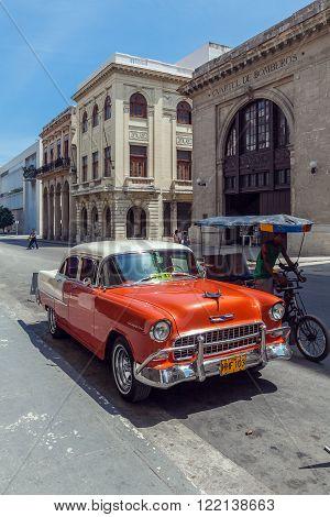 HAVANA, CUBA - APRIL 1, 2012: Orange Chevrolet vintage car in front of Museo de los Bomberos
