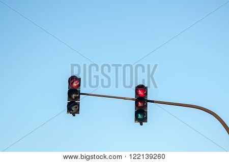 two traffic lights showing red in all directions against the blue sky with a generous copy space concept for resistances no legal way out or dangerous paths in life or business