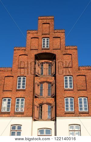typical historic storehouse with crow-stepped gable in red brick architecture, tourism attraction  in the hanseatic old town of Luebeck against the blue sky, Europe, North Germany