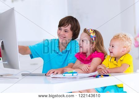 School kids working on personal computer at home. Student doing homework using modern pc in classroom. Kids studying with digital devices. Children study in white class room. Child learning.