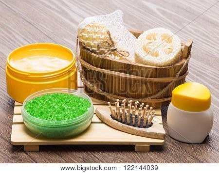 Spa and pampering products and accessories. Green coarse sea salt, massager, wooden basket with loofah, body scrubber and pumice, natural body scrub, skin care cream on wooden surface