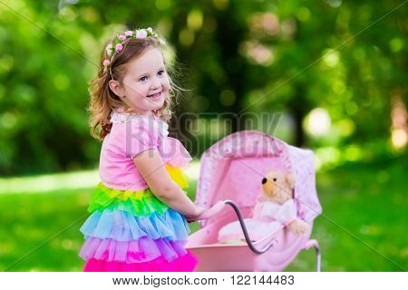Little girl pushing toy stroller with bear. Toddler kid in pink dress playing with doll buggy. Kids birthday party. Children play outdoors. Mother and baby role game. Family summer fun. Preschool toys