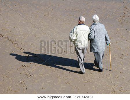Elderly couple walking on beach on sunny day