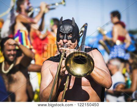 Rio de Janeiro, Brazil - February 9, 2016: Masked musician playing the trombone with Bloco da Orquestra Voadora during Carnaval 2016 parade in Rio de Janeiro, Brazil.