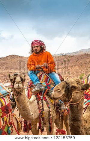 Petra, Jordan - October 26, 2015: Bedouin on a camel. A walk on a camel. The service for tourists. Tour guide. The rainy season in Jordan. Petra is one the New Seven Wonders of the World.