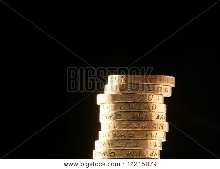 Stack of UK pound coins over black