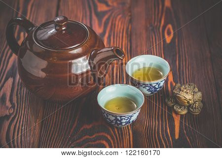 Broun ceramic teapot and two cups for the tea ceremony on rustic wooden table
