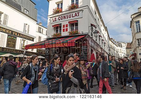 PARIS FRANCE-OCTOBER 10 2015: Crowds of tourists in the narrow streets and lively in Montmartre Paris France.View of typical Paris cafe. Montmartre area is among most popular destinations in Paris