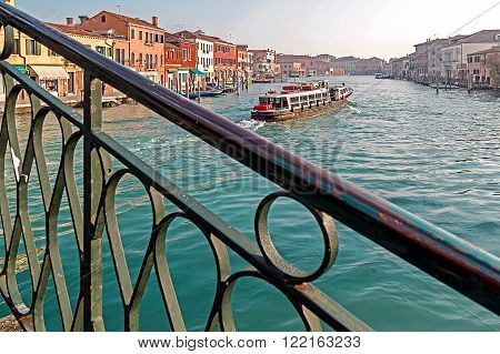 MURANO ITALY - JANUARY 25 2016: Venice Italy Murano water boats canal and traditional buildings.117 islands separated by canals and bridges. Murano is glass making island. World Heritage Site.