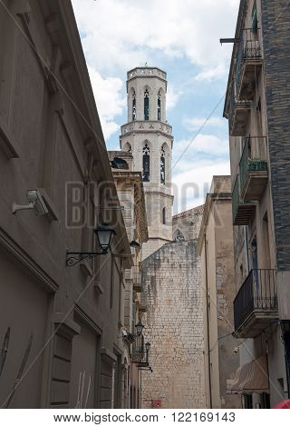 Old buildings on old Llers Street with Church of Sant Pere in the end of it in Figueres Catalonia Spain.