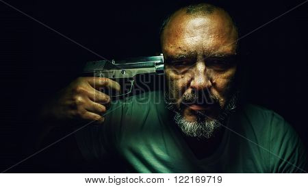 Portrait of a hard depressed man, holding a pistol on his forehead.