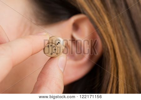 Woman Hands Putting Hearing Aid In Ear
