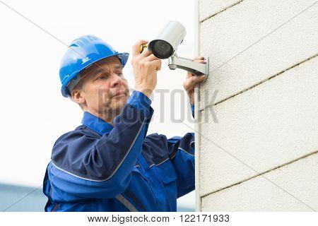 Male Technician Fixing Cctv Camera On Wall