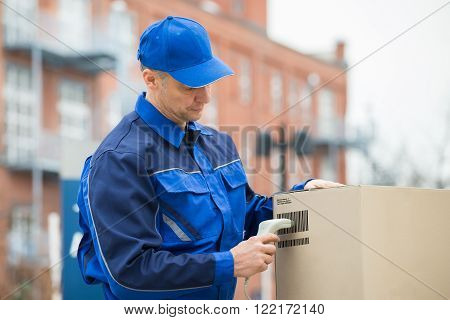 Delivery Man Scanning Cardboard Boxes With Barcode Scanner