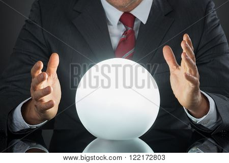 Close-up Of Businessman Hand On Crystal Ball