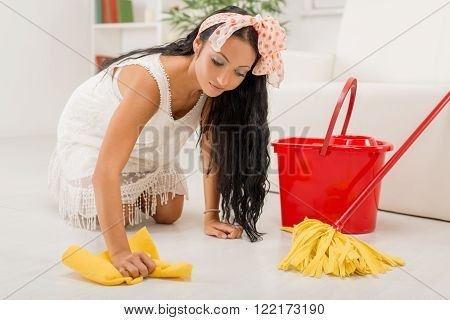 Young beautiful maid scrubbing floor in the home poster