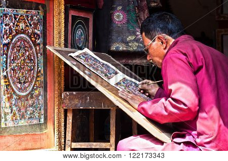 BHAKTAPUR, NEPAL - APR 05: Nepalese artist creates traditional mandala painting on Apr 05, 2014 in Bhaktapur, Nepal.