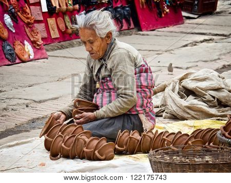 BHAKTAPUR, NEPAL - APR 5: Unidentified Nepalese woman working at the pottery market, Apr 5, 2014 in Bhaktapur, Nepal.