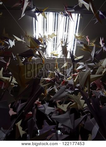 Handmade colored origami cranes on ceiling strings under light lamp