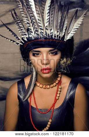 young pretty woman with make up like American indian, feather in hair, fashion hallowen concept creative