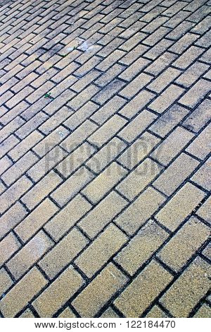 Full frame brick pavement close up from low tilted angle in vertical 3:2 format.