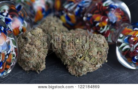 Granddaddy Purple medicinal medicinal marijuana close up of buds surrounded by colorful glass.