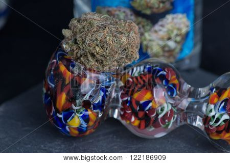 Grandaddy Medicinal Medical marijuana in colorful glass pipe. ** Note: Shallow depth of field