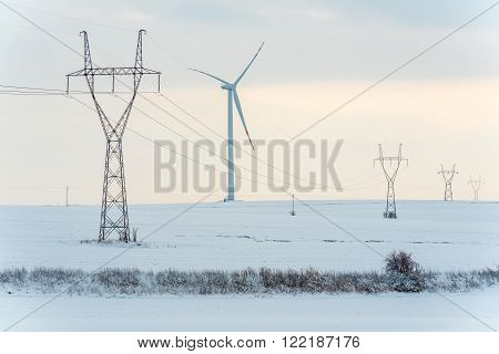 Large view on the windmill and powerlines on the field in winter season