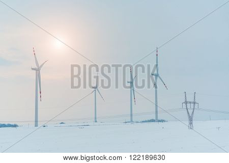 Sunset above the windmill and powerlines on the field in winter season