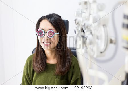 Woman checking vision with trial frame at eye clinic