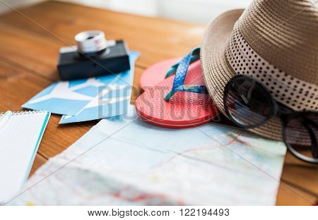 summer vacation, tourism and objects concept - close up of travel map, flip-flops, hat and camera with airplane tickets on wooden table at home