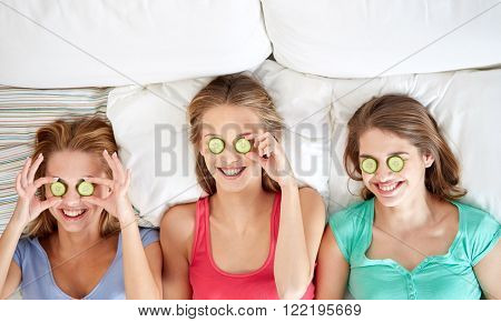 people, beauty, natural cosmetics and pajama party concept - happy friends or teenage girls with cucumber mask having fun and lying in bed at home