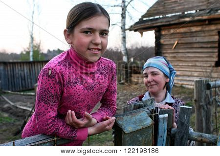 Lipovec village Tver region Russia - May 1 2006: Peasant girl Tanya 11 years old standing at the fence near the farmhouse not far from his mother spring evening.