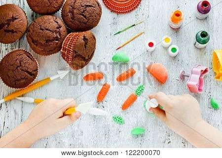 Easter carrot cakes cook. Kid hands make marzipan carrots for decoration cakes on a white table. Creative idea for Easter baking top view