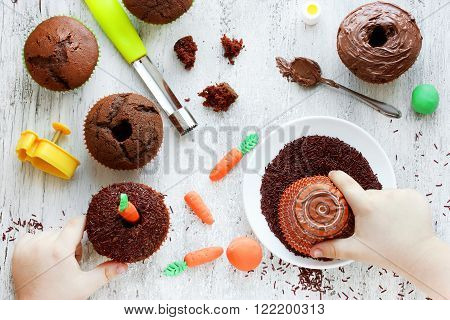 Easter carrot cakes cook. Kid hands decorated cupcakes chocolate sprinkles on a white table. Creative Easter baking cooking process with a child in the kitchen
