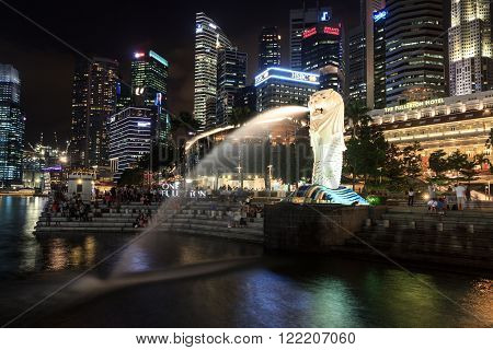 Singapore, Singapore - May 18, 2015: The Merlion statue and Singapore skyline at night. The Merlion is a traditional creature in Singapore with a lions head and a body of fish.