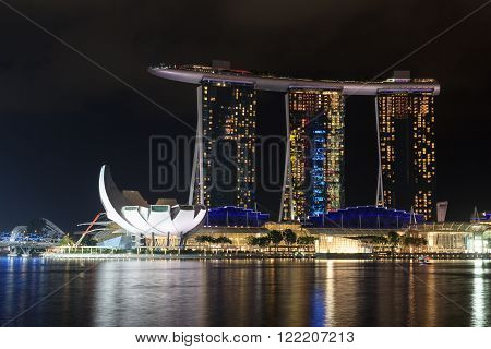 Singapore, Singapore - May 18, 2015: Marina Bay Sands hotel and ArtScience museum at night in Singapore. The hotel is a luxury resort famous for its infinity swimming pool and a landmark in Singapore.