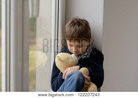 Thoughtful little boy sitting on the windowsill and hugs his favourite teddy bear. Rainy day
