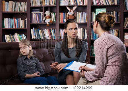 Young mom with her daugher at psychologist consultation