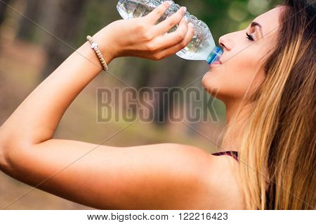 Picture of a Yound sexy blonde girl drinking water after jogging