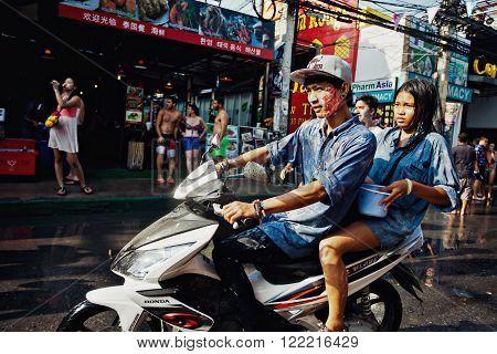 KO SAMUI, THAILAND - APRIL 13: Unidentified thai people on a bike on Songkran Festival (Thai New Year) on April 13, 2014 in Chaweng Main Road, Ko Samui island, Thailand.